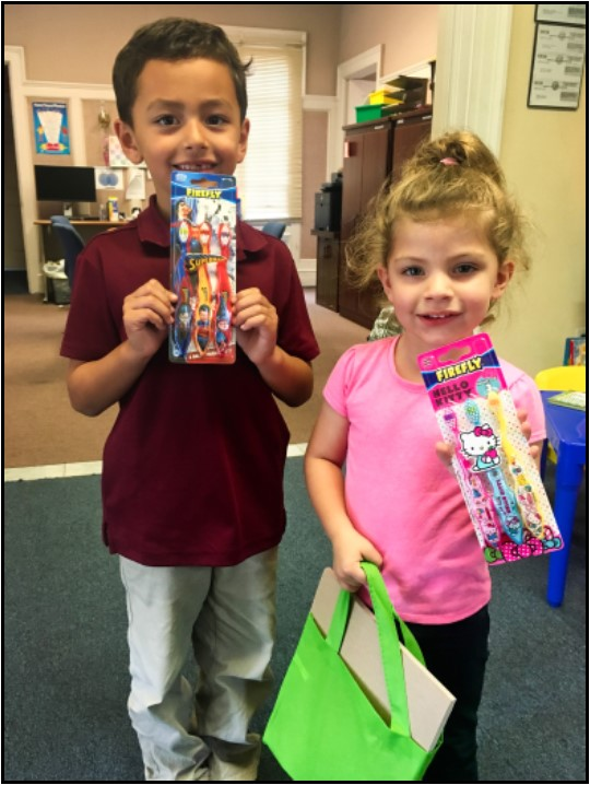 Happy children display their new dental hygiene products (toothbrushes, in this case); gifts from the Orange County Childhood Language Center.